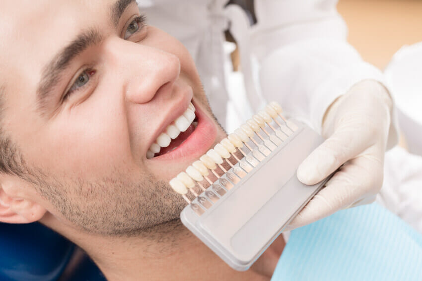 Man smiling while sitting in dental chair receiving cosmetic dentistry services