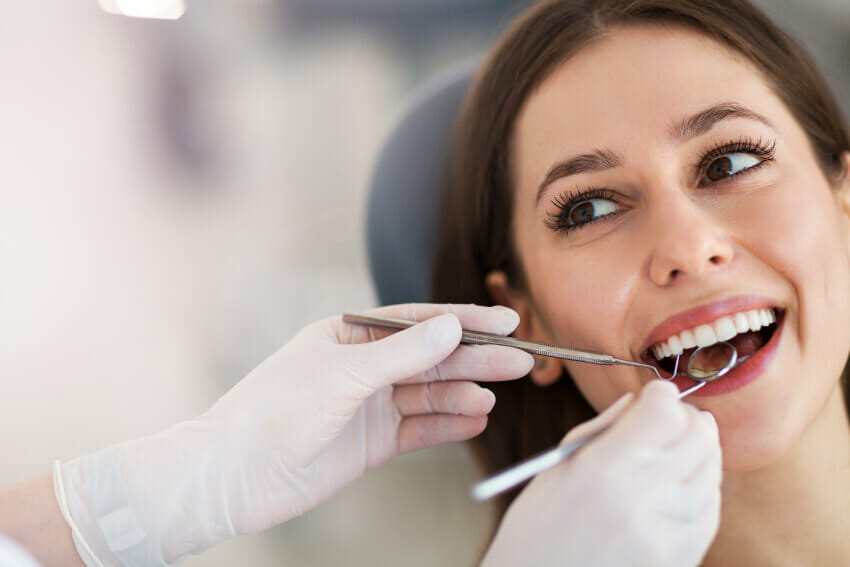 Woman in dentist chair receiving crown lengthening