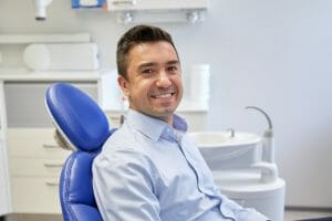 Man smiling in dental chair awaiting a dental extraction