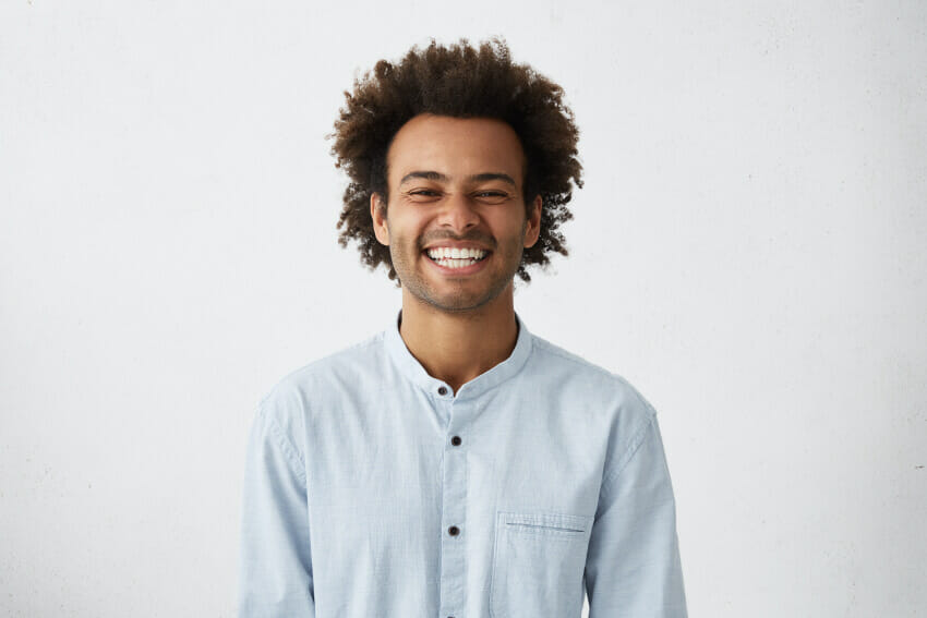 Man with curly brown hair, button up shirt smiling