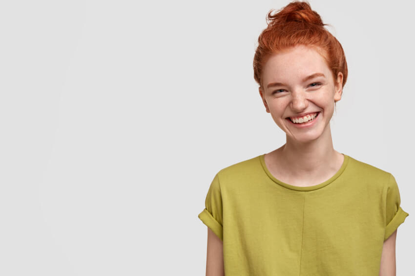 Woman with red hair and green shirt smiling
