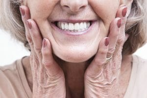 Woman clutching jaw after receiving implant supported dentures