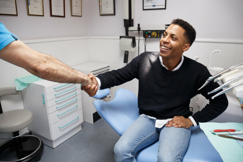 Young man in black shirt shaking hands with dentist