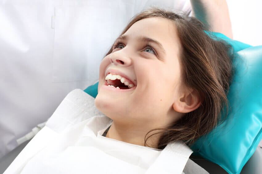 Young girl sitting in dental chair smiling awaiting her new sealants