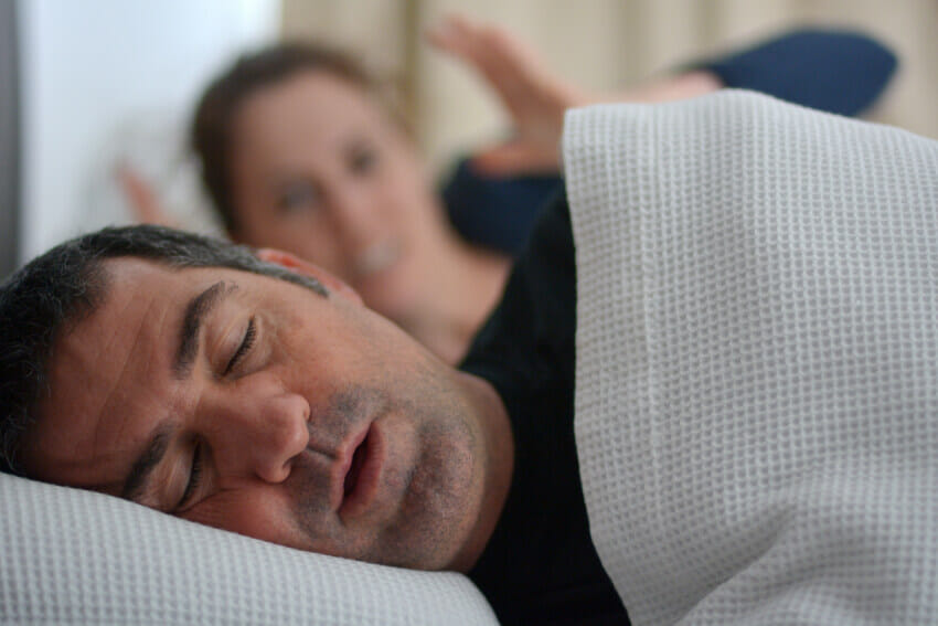 Man sleeping in be but suffering from sleep apnea