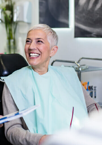 Woman laughing while sitting in dental chair